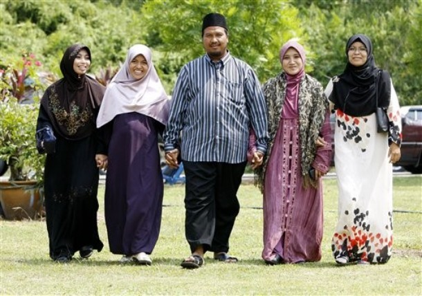 "In this  Aug. 15, 2009 photo, polygamist Mohammad Inaamulillah Bin Ashaari, center, is shown with his four wives, from left, Rohaiza Esa, Ummu Habibah Raihaw , Nurul Azwa Mohd Ani,and Ummu Ammarah Asmis at the ""Ikhwan Polygamy Club Family Day"" in Rawang, north of Kuala Lumpur, Malaysia. Polygamy is legal for Muslims in Malaysia, though not widespread. The Ashaari clan believes it should be. Last month, the sprawling family launched a Polygamy Club that seeks to promote plural marriages for what it says are noble aims, such as helping single mothers, prostitutes and older women find husbands. (AP Photo/Mark Baker)"