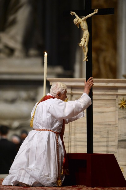 Pope Benedict XVI bows in front of the cross during the Celebration of the Lord's Passion on Good Friday on April 6, 2012 St Peter's basilica at The Vatican. Christians mark the crucifixion of Jesus Christ on Friday in a series of ceremonies culminating on Sunday, when they celebrate Christ's resurrection. AFP PHOTO / VINCENZO PINTO (Photo credit should read VINCENZO PINTO/AFP/Getty Images)